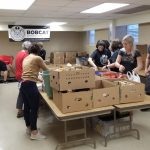 Photograph of people packing boxes of supplies