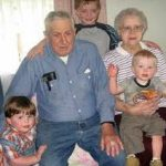 Photograph of two grandparents surrounded by children